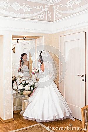 La jeune mari e dans la robe de mariage regarde dans le for Regard dans le miroir