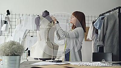 La jeune ouvrière couturière attirante mesure le simulacre du ` s de tailleur avec la bande pour faire le nouveau vêtement avec c banque de vidéos