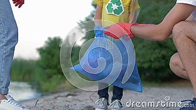La limpieza de la caridad, familia joven con el niño en los guantes de goma recoge la basura en bolso de basura en la playa sucia almacen de video