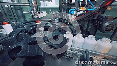 La máquina industrial es casquillos que atornillan a los tarros plásticos almacen de metraje de vídeo