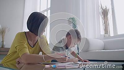 La mère dans la guêpe et le fils dans le T-shirt s'asseyent à la table et réunissent des crayons de couleur sur le papier Enfance banque de vidéos