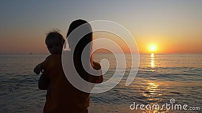 La mère tient le bébé dans ses bras en regardant le coucher du soleil sur la mer ou sur la côte océanique banque de vidéos