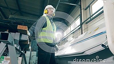 La macchina in fabbrica sta piegando i bordi del metallo sotto il controllo del lavoratore stock footage