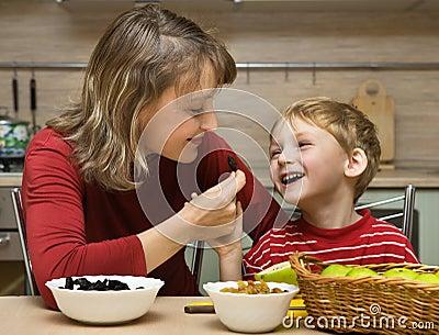 La madre con el niño es fruta comida en cocina