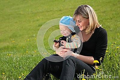 La madre con el niño se sienta en hierba