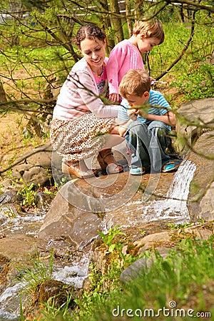 La madre con los niños mira en poca cascada