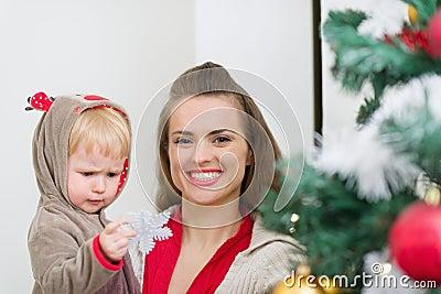 La madre de ayuda del bebé adorna el árbol de navidad