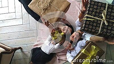 La madre, el padre, el hijo, y la hija felices hermosos de la familia con los regalos en las manos están en el piso metrajes