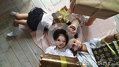 La madre, el padre, el hijo, y la hija felices hermosos de la familia con los regalos en las manos están en el piso almacen de video