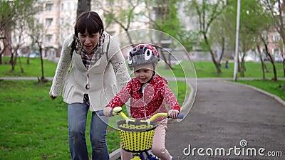 La madre enseña a la pequeña hija a montar una bicicleta almacen de video