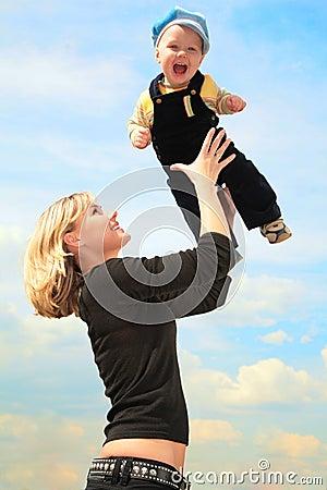 La madre levanta al niño en las manos al aire libre