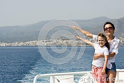 La madre, niño disfruta del viento y del viaje por mar en el barco