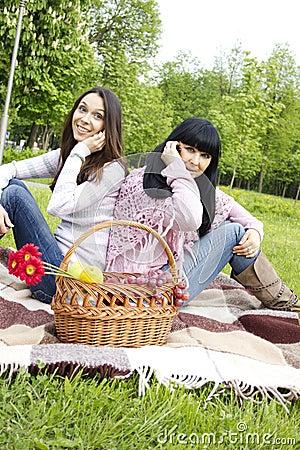 La madre y la hija hablan en el teléfono en el parque
