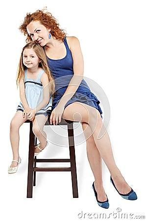 La madre y la hija se sientan en taburete
