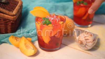La main de la femme a mis un verre avec le thé glacé doux de pêche faite maison fraîche ou le cocktail, limonade avec la menthe B clips vidéos