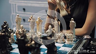 La main femelle jouant des échecs, met le chiffre de cheval à bord clips vidéos