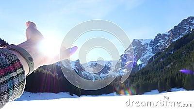 La main s'étend au soleil et aux montagnes Le concept de la lueur du soleil de la paume banque de vidéos