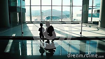 La maman et le bébé vont à la fenêtre à l'aéroport pour regarder l'avion dans le mouvement lent banque de vidéos
