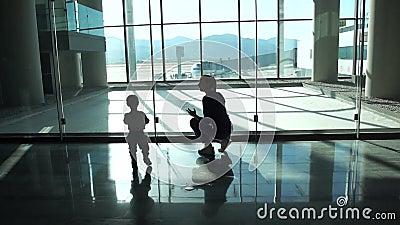 La maman et le petit garçon vont à la fenêtre au hall d'aéroport pour regarder l'avion banque de vidéos