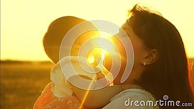 La mamma felice gioca con il bambino, madre getta il bambino in aria nei raggi luminosi del sole Primo piano lento della fucilazi archivi video