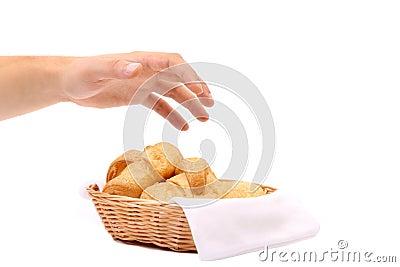 La mano alcanza para los cruasanes en una cesta.