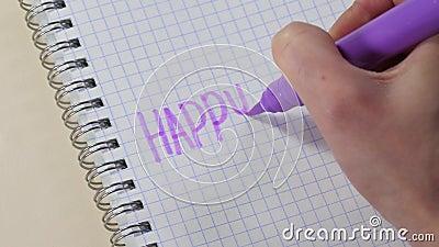 La mano de una mujer escribe la palabra 'familia feliz' con un marcador morado en un billete almacen de metraje de vídeo