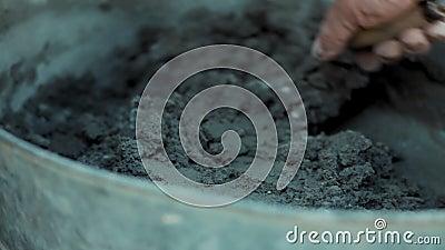 La mano del constructor amasó la solución del cemento en barril de hierro almacen de video