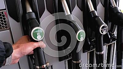 La mano del hombre pone la boquilla del combustible en la gasolinera metrajes