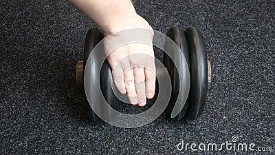 La mano del hombre toma un pesado timbre en el gimnasio, cierra el deportista interior almacen de metraje de vídeo