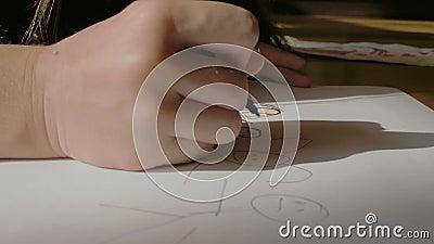 La mano di un bambino attira uomini piccoli su un foglio di carta seduto sul pavimento disegno di un'immagine video 4k lento stock footage