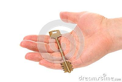 La mano lleva a cabo la llave de acero de bronce.