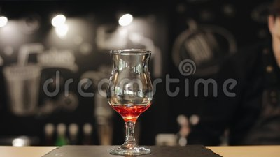 La mano masculina del barista vierte el jarabe rojo y pone las hojas de menta en un vidrio vacío en un contador de la barra almacen de metraje de vídeo