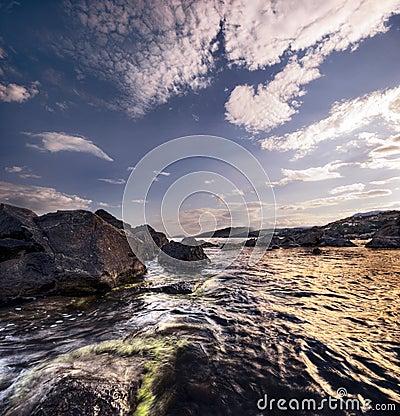 La mer, le soleil, nuages, pierres