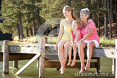 La mère, le descendant et le grand-mère se sont assis par le lac