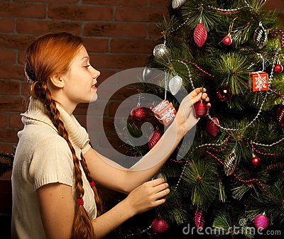 La muchacha adorna el árbol de navidad