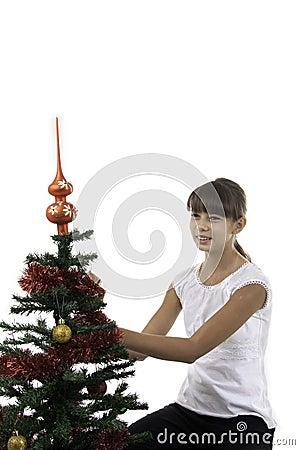 La muchacha adorna un árbol del Año Nuevo