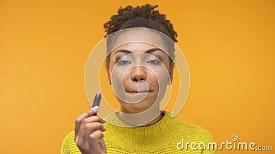 La muchacha afroamericana bonita que aplica la barra de labios y que guiña, alista para la fecha almacen de video