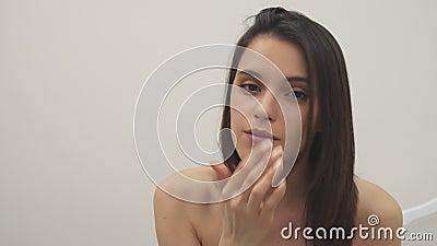 La muchacha aplica el tratamiento facial almacen de metraje de vídeo