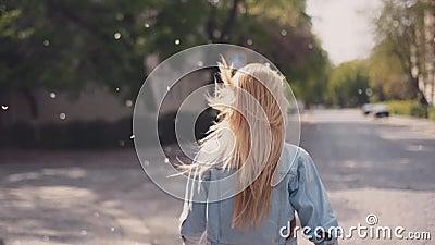 La muchacha atractiva se está preguntando abajo de las calles, da vuelta a la cámara y las sonrisas, tiempo ventoso, flor de los  almacen de video