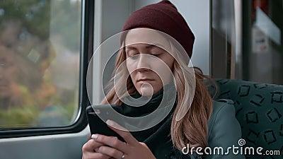 La muchacha cauc?sica joven en un casquillo rojo monta en un subterr?neo o el coche de tren de la tranv?a, utiliza el tel?fono, i almacen de video