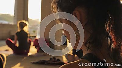 La muchacha de la yogui está meditando en grupo en el edificio abandonado en verano en la salida del sol, forma de vida sana, con metrajes