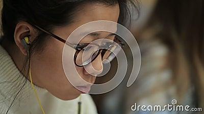 La muchacha del aspecto asiático en vidrios y de auriculares en oídos lee metrajes