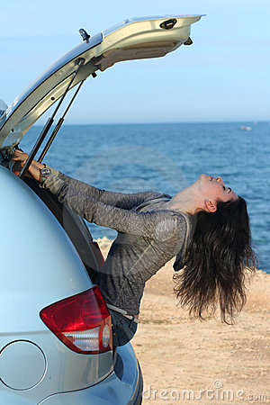 La muchacha en un portador de equipaje del coche