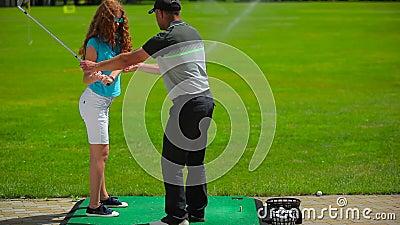 La muchacha entrena para golpear la bola en golf metrajes