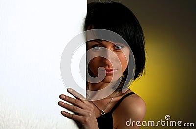 La muchacha está mirando hacia fuera-de la tarjeta vacía blanca
