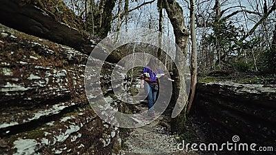 La muchacha feliz hermosa camina en la grieta de la montaña en el día soleado almacen de metraje de vídeo