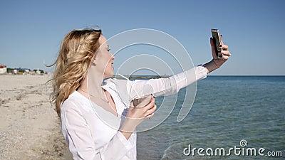 La muchacha hace la memoria del selfie, muchacha atractiva cerca del agua en la cámara lenta, almacen de metraje de vídeo