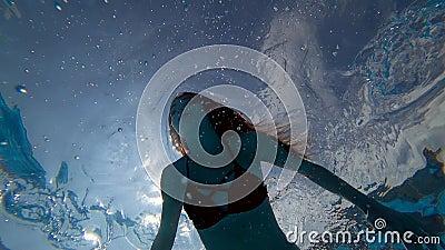 La muchacha hermosa con los ojos abiertos flota bajo el agua en la piscina azul clara en burbujas del fondo almacen de metraje de vídeo