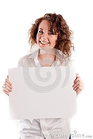 La muchacha hermosa joven lleva a cabo una muestra blanca vacía para que usted complete