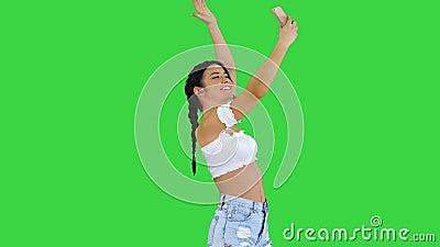 La muchacha morena linda toma un selfie y el baile en una pantalla verde, llave de la croma almacen de metraje de vídeo